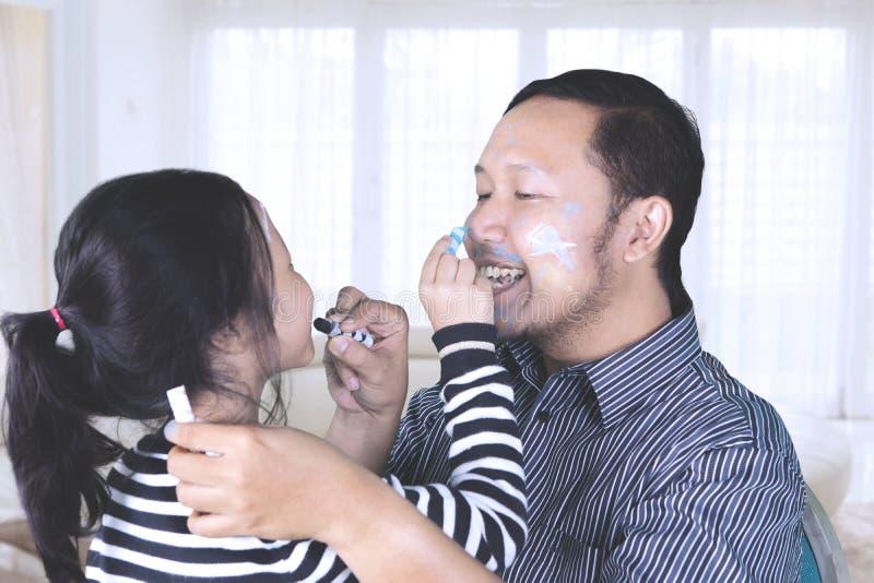 Aziatische mens met kind die gezicht het schilderen doen stock foto