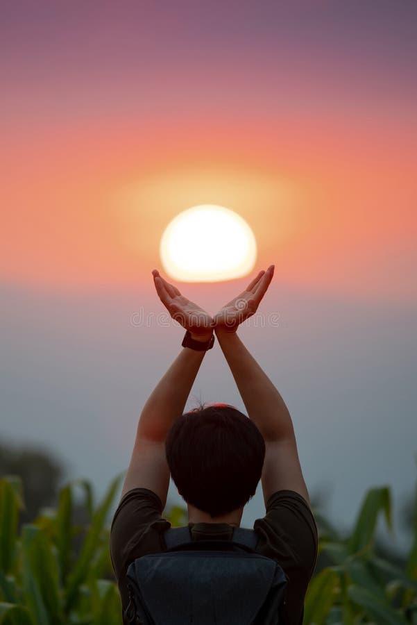 Aziatische mens op graangebied die de zon houden stock afbeelding