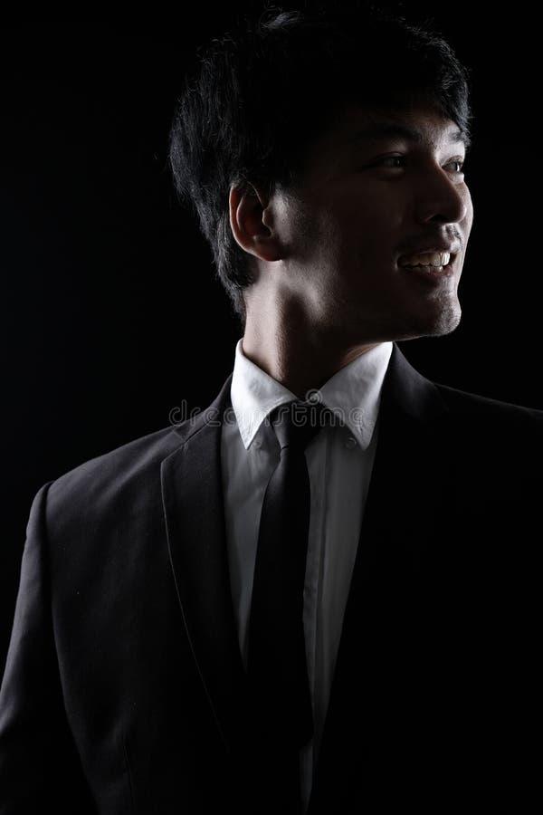 Aziatische mens in zwart formeel kostuum in dark royalty-vrije stock foto's