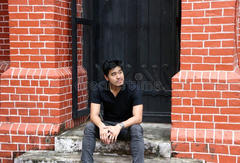 Aziatische mens in zwarte overhemdszitting voor een zwarte deur tussen twee baksteenpijlers stock fotografie