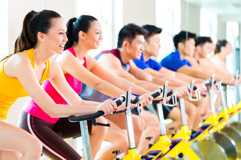 Aziatische mensen die fiets opleiding spinnen bij geschiktheidsgymnastiek stock afbeelding