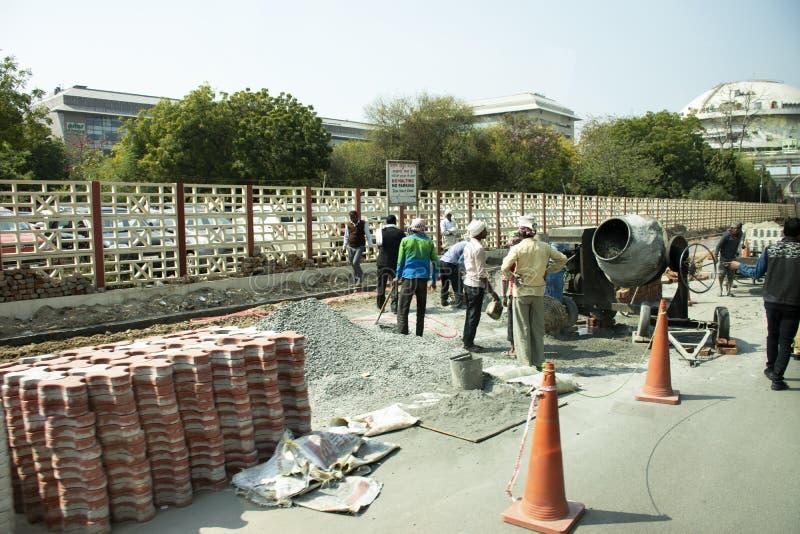 Aziatische mensen en Indische arbeiders met het zware nieuwe voetpad van de machines werkende bouwer bij bouwwerf in New Delhi, I royalty-vrije stock afbeeldingen