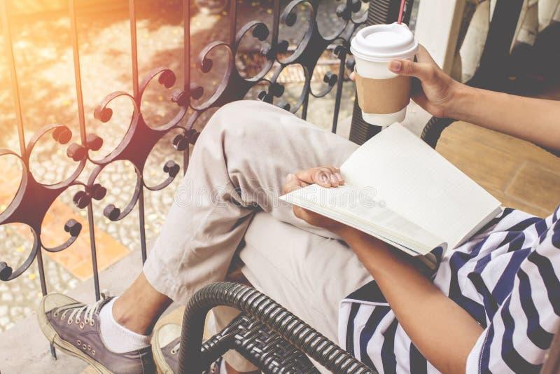 Aziatische mensen knappe gebaard in blauw overhemd en het dragen van glazenzwarte Mensenzitting in de lezingsboek van de koffiewi stock foto's