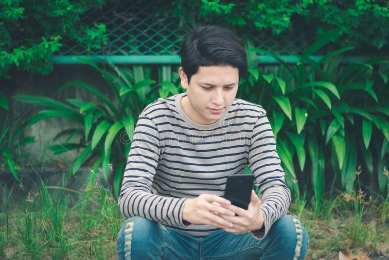 Aziatische mensenzitting en het gebruiken van smartphone stock afbeeldingen