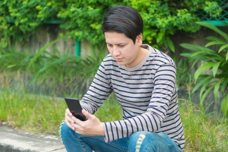 Aziatische mensenzitting en het gebruiken van smartphone royalty-vrije stock afbeelding