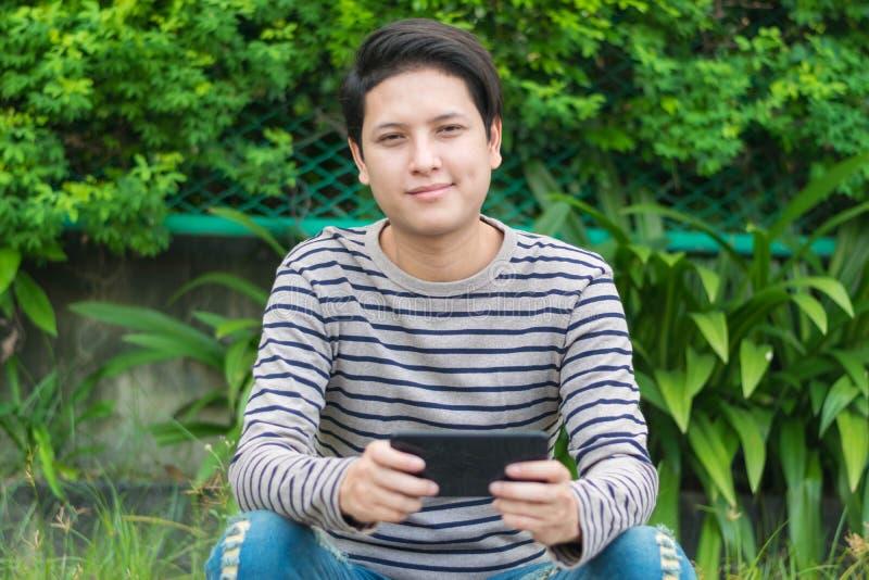 Aziatische mensenzitting en het gebruiken van smartphone stock fotografie