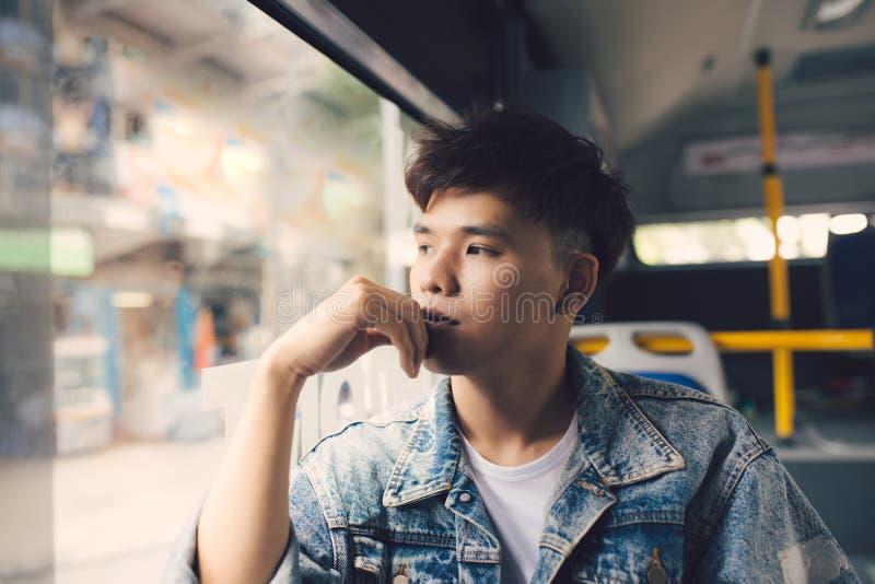 Aziatische mensenzitting in stadsbus die door venster kijken stock foto