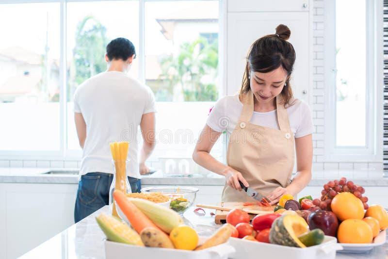 Aziatische minnaars of paar kokende en snijdende groente in keuken stock foto
