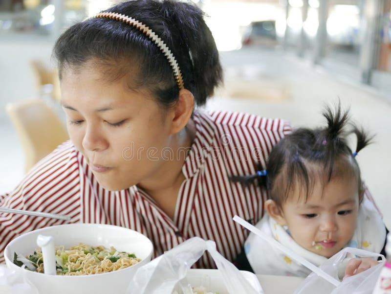 Aziatische moeder allebei voeden zelf en haar babymeisje, één éénjarige die stock fotografie