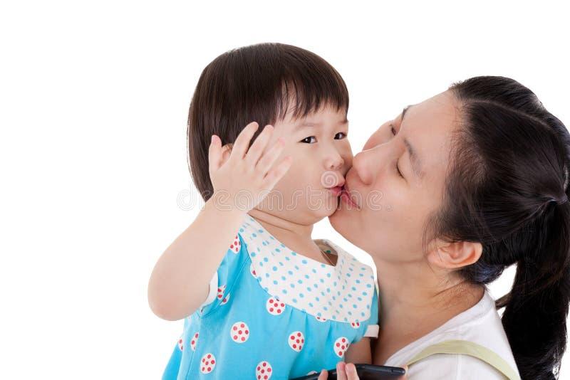 Aziatische moeder die en haar dochter op witte backgr vervoeren knuffelen stock afbeelding