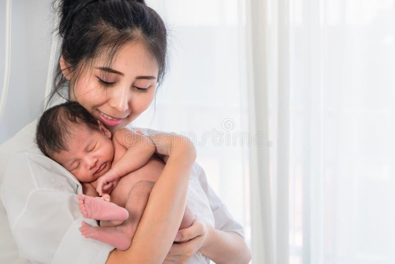 Aziatische moeder die haar jongen van de zuigelingsbaby op hand met geluk houdt royalty-vrije stock afbeeldingen