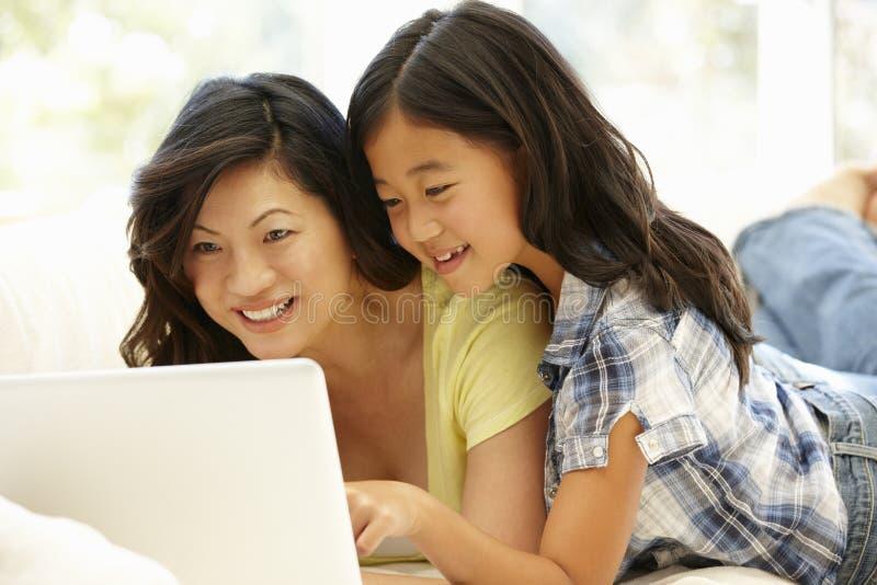 Aziatische moeder en dochter die laptop thuis met behulp van stock foto