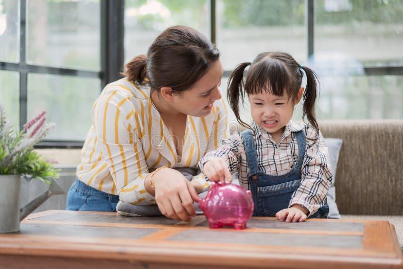 Aziatische moeder en weinig dochter die muntstukken zetten in spaarvarken stock afbeelding