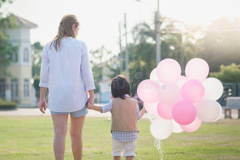 Aziatische moeder en zoonsholdingshand samen en lopend royalty-vrije stock afbeelding