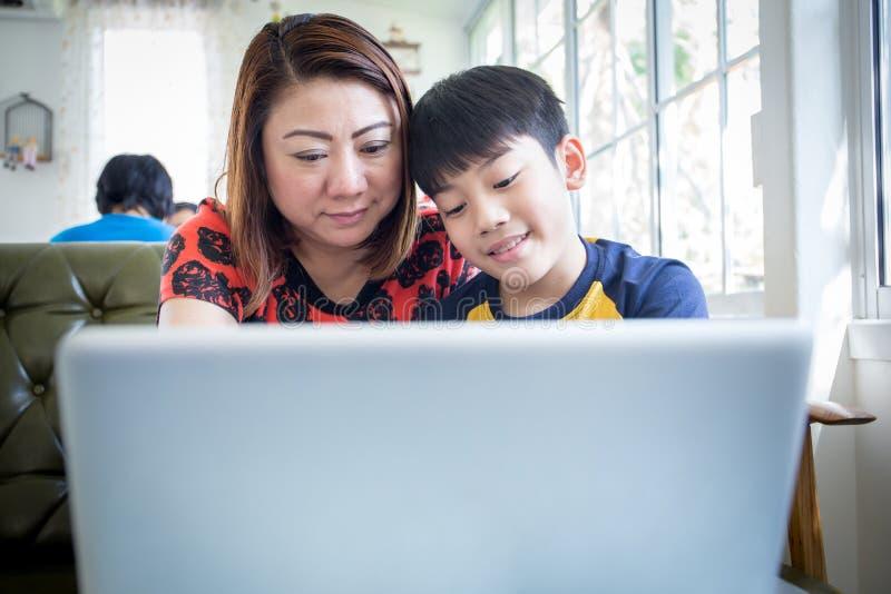 Aziatische Moeder en Zoonszitting bij Bureau die Laptop thuis met behulp van royalty-vrije stock fotografie