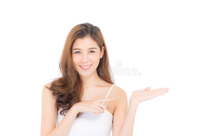 Aziatische mooie jonge vrouw die met gezonde schone huid tonen die iets voorstellen lege exemplaarruimte stock foto's