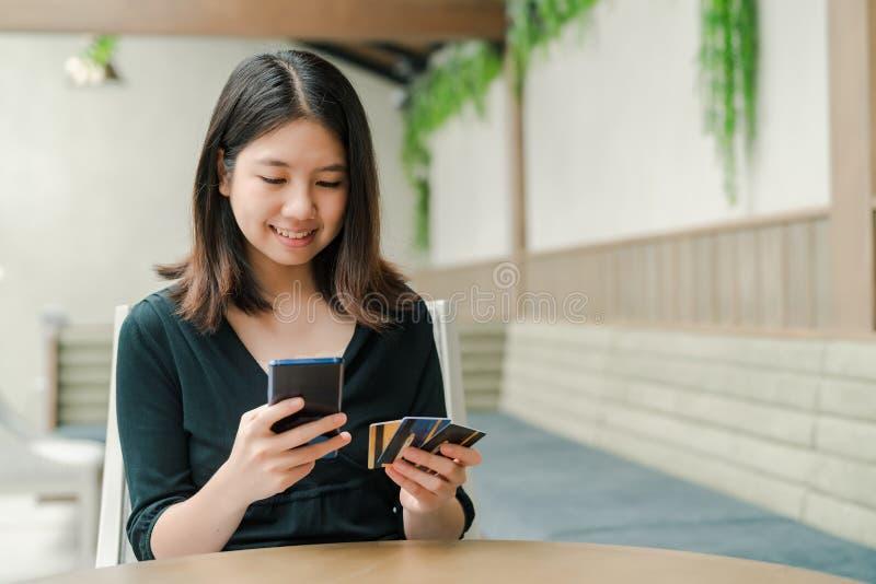 Aziatische mooie vrouw die een zwarte overhemdszitting in het huis dragen is Er een creditcard in uw hand en u houdt de telefoon royalty-vrije stock fotografie