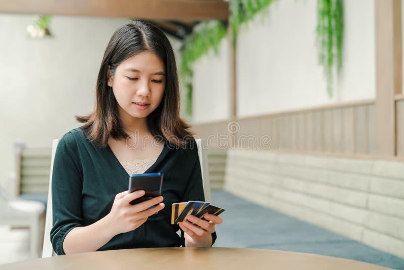 Aziatische mooie vrouw die een zwarte overhemdszitting in het huis dragen is Er een creditcard in uw hand en u houdt de telefoon stock afbeeldingen