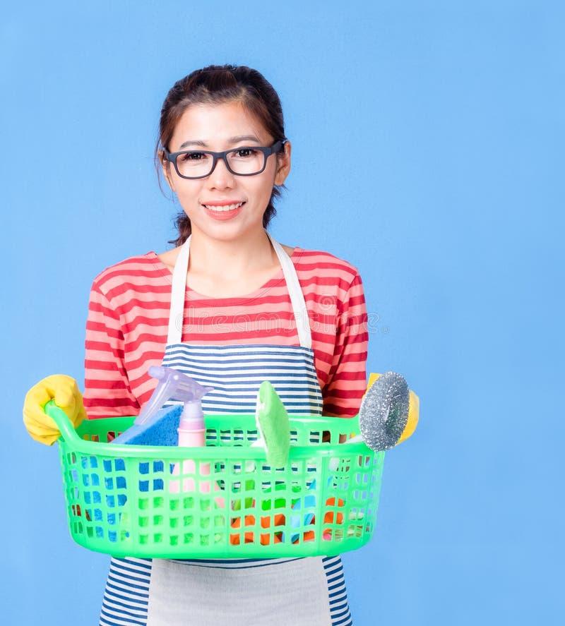 Aziatische mooie vrouw houdt een mand vast om het apparaat schoon te maken en lacht gelukkig om het huis schoon te maken royalty-vrije stock afbeelding