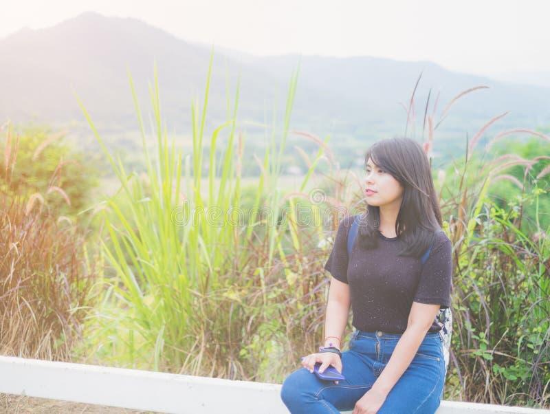 Aziatische Mooie Vrouwen Draag een toevallige kledings zwarte t-shirt met Jeans Het zitten op een witte omheining stock afbeelding