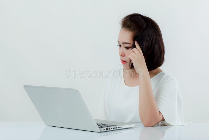 Aziatische mooie vrouwenzitting in een wit overhemd op het voorbureau, is er een laptop geplaatste computer Uitdrukking is Er het royalty-vrije stock fotografie