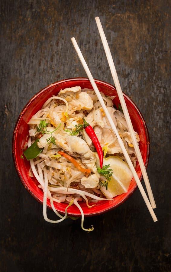 Aziatische noedels met eetstokje, kip en spruiten op donkere houten achtergrond stock afbeelding
