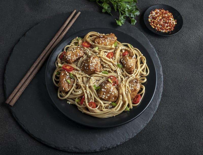 Aziatische noedels met kippenteriyaki, sesam, rustieke steenachtergrond close-up Chinese/Japanse noedels stock afbeeldingen
