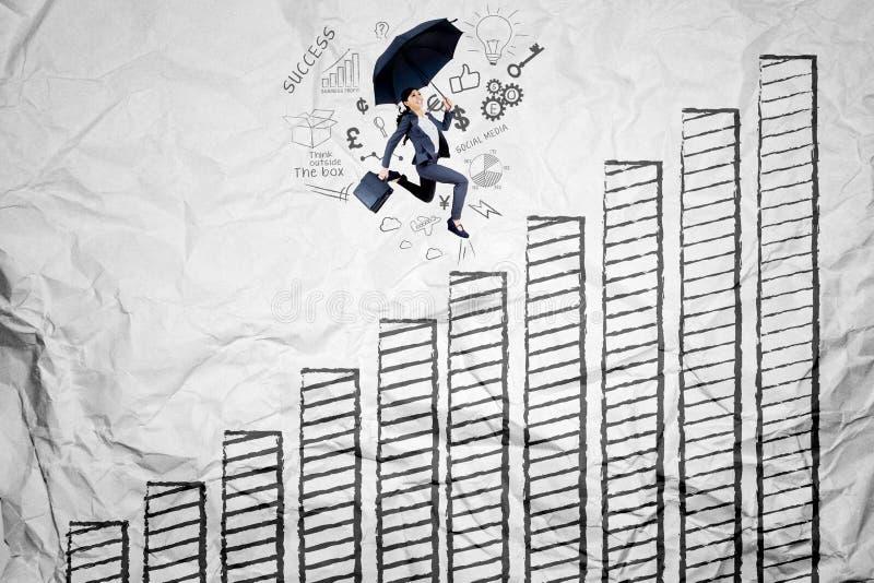 Aziatische onderneemster die boven de groeigrafiek lopen stock foto's