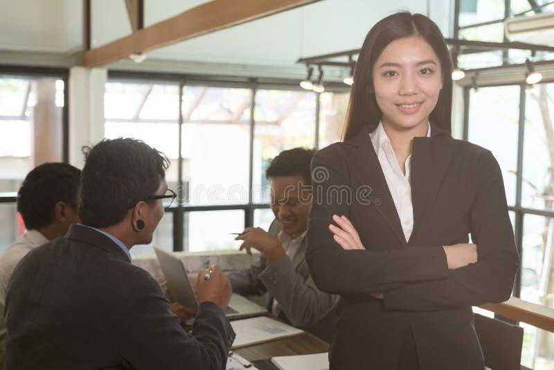 Aziatische onderneemster die met gevouwen handen bij camera glimlachen confide royalty-vrije stock foto