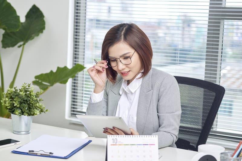 Aziatische onderneemster die met tabletcomputer bij bureau werken stock foto's