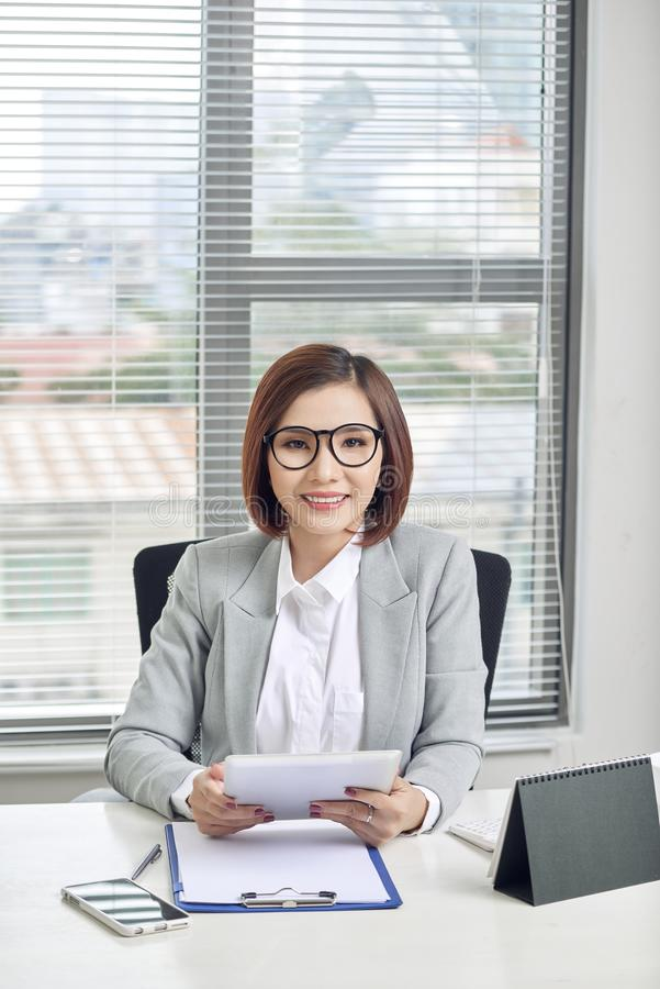 Aziatische onderneemster die met tabletcomputer bij bureau werken royalty-vrije stock foto's