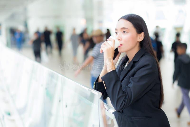 Aziatische onderneemster die mobiele telefoon spreken en een koffiekop houden stock foto