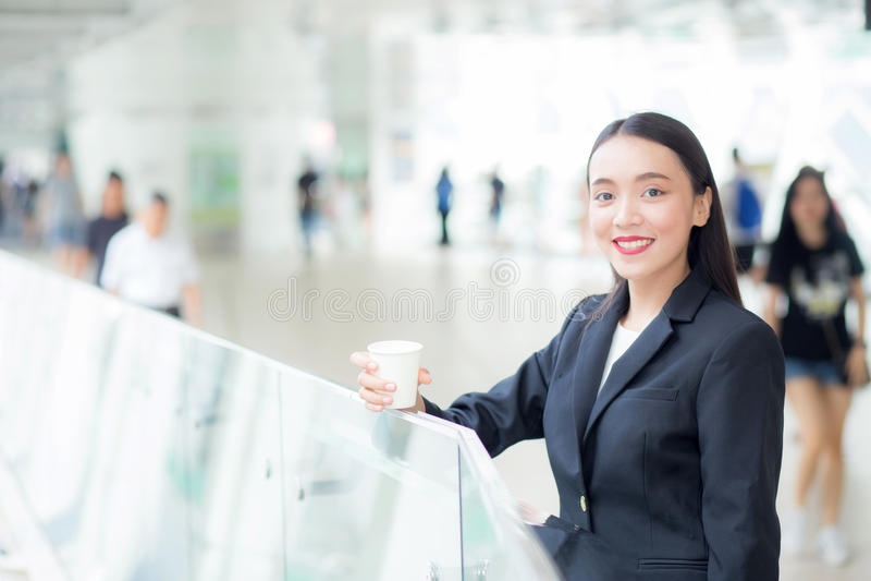 Aziatische onderneemster die mobiele telefoon spreken en een koffiekop houden stock afbeelding