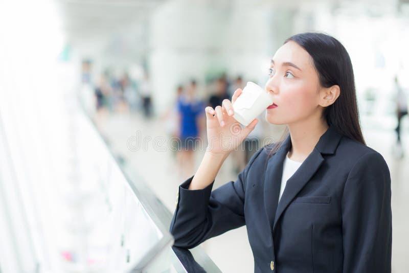 Aziatische onderneemster die mobiele telefoon spreken en een koffiekop houden royalty-vrije stock afbeelding