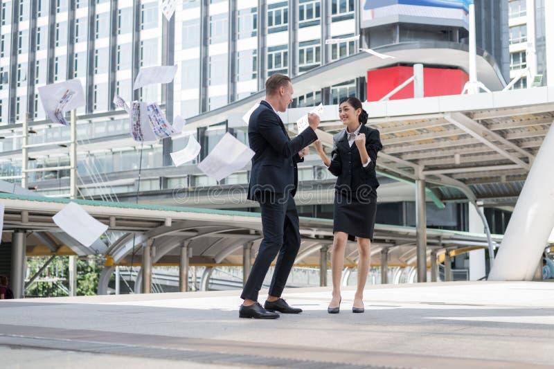 Aziatische onderneemster en Kaukasische zakenman die document in de lucht werpen en op handen aan gevierd voor volledige opdracht stock foto