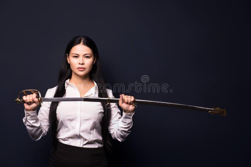 Aziatische onderneemster met zwaard stock foto's