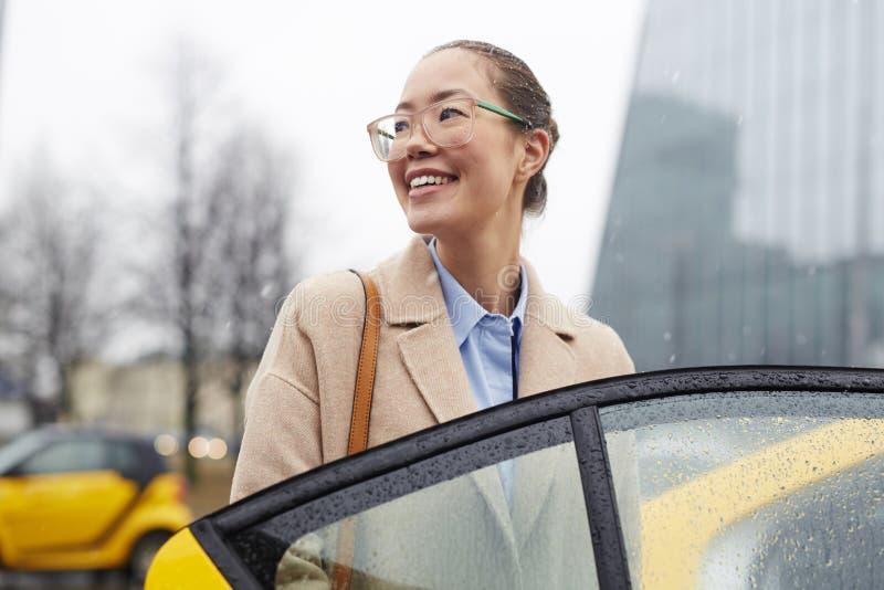 Aziatische Onderneemster Taking Taxi in Regenachtige Straat stock foto's