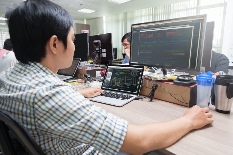 Aziatische Ontwikkelaar die Laptop Computerzitting gebruiken stock fotografie