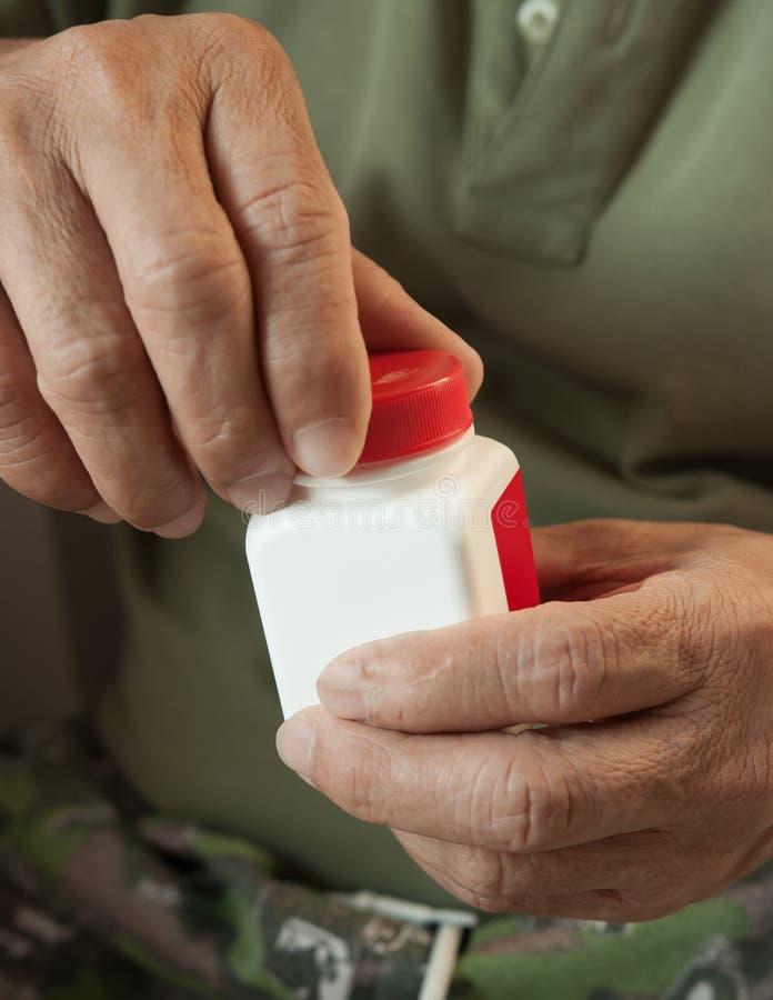 Aziatische oude mens die de fles geneeskunde openen stock foto