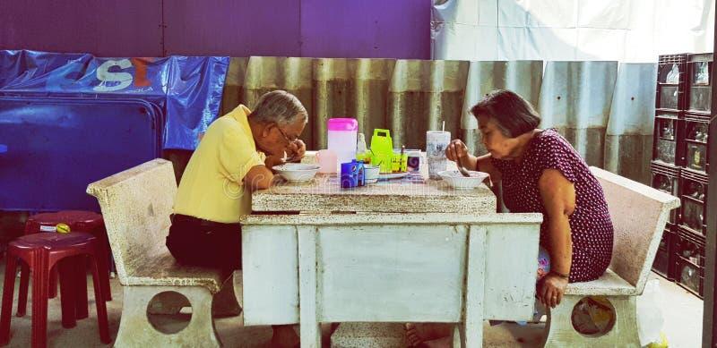 Aziatische Oudere mensen of Echtgenoot en vrouw die noedel eten bij Thais lokaal straatvoedsel royalty-vrije stock afbeelding