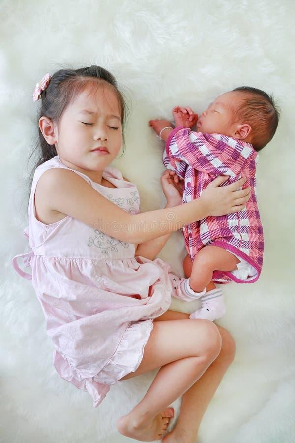 Aziatische oudere zuster en de pasgeboren slaap van de babyjongen samen op witte bontachtergrond stock fotografie