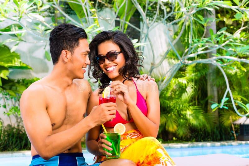 Aziatische paar het drinken cocktails bij pool royalty-vrije stock fotografie