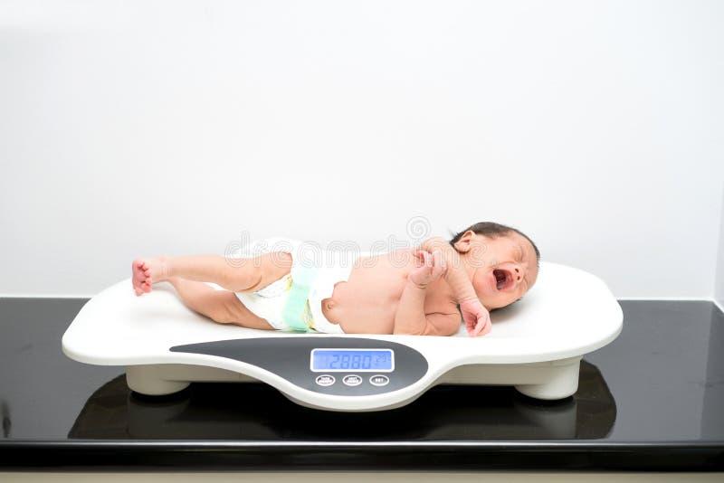 Aziatische pasgeboren baby die op de schalen leggen stock afbeeldingen