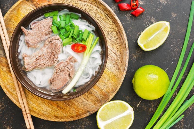 Aziatische pho van de schotel Vietnamese soep Vietnamese soep met rijstnoedels, vlees en groene uien op een donkere achtergrond M stock foto's