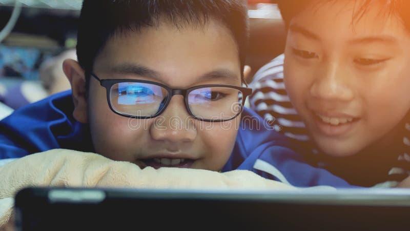 Aziatische preteens die op tabletcomputer letten op, glimlachgezicht stock afbeeldingen
