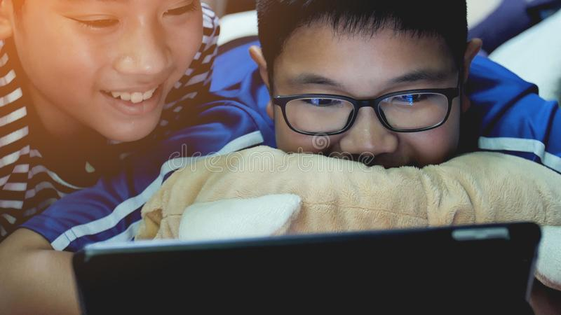 Aziatische preteens die op tabletcomputer letten op, glimlachgezicht stock fotografie