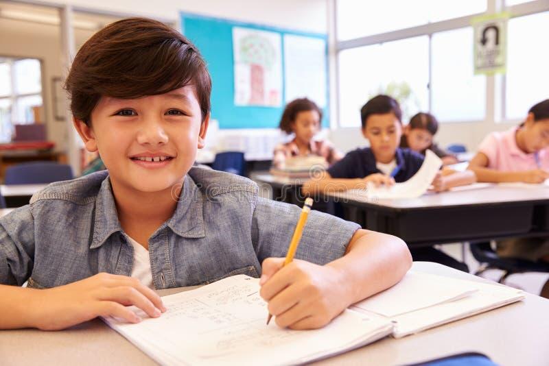 Aziatische schooljongen die in basisschoolklasse aan camera kijken stock foto