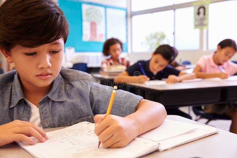 Aziatische schooljongen die in basisschoolklasse werken stock foto's