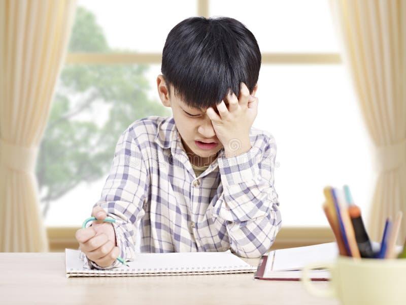 Aziatische schooljongen die thuis bestuderen stock afbeeldingen
