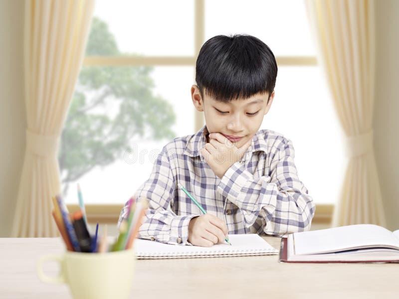 Aziatische schooljongen die thuis bestuderen royalty-vrije stock afbeeldingen